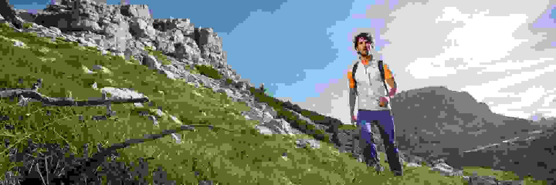 ein Mann wandert auf einem grünbewachsenem Berggipfel.