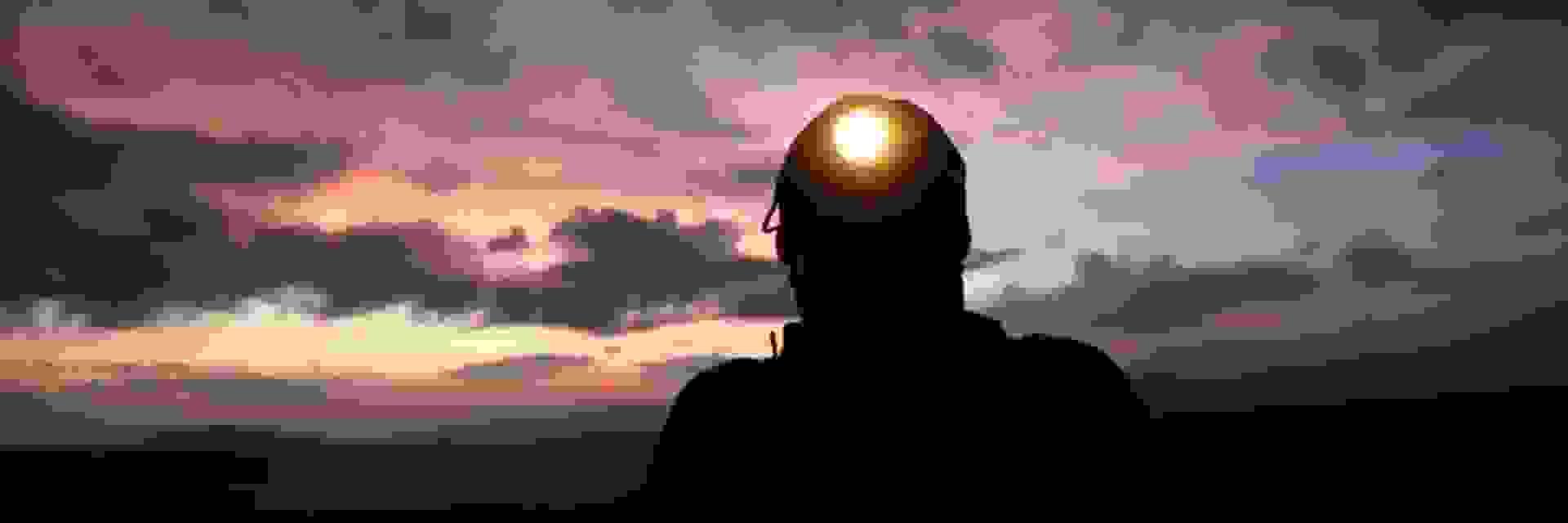 Ein Mann schaut im Dunkeln mit einer eingeschalteten Stirnlampe in die Kamera.