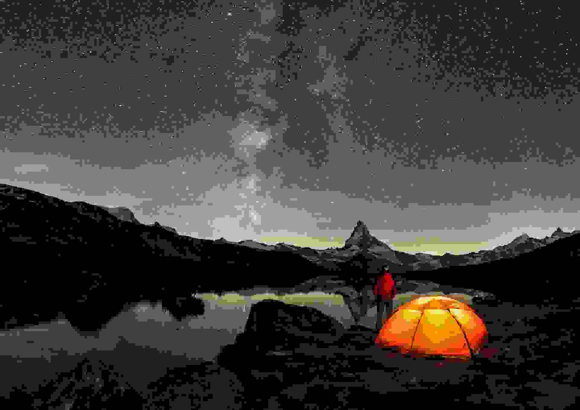 Ein Zelt steht in der Nacht vor dem Matterhorn.