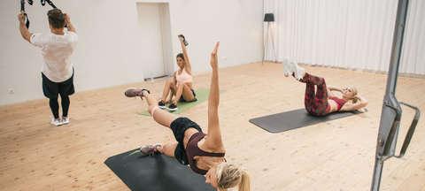 Eine Gruppe trainiert in einem Fitnessstudio - mit TRX Bänder, Situps, Hanteln und Planks.