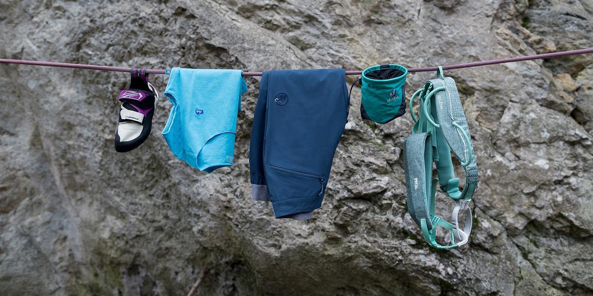 Diverse Bekleidungs- und Ausrüstungsgegenstände zum Klettern auf einem Seil aufgehängt.