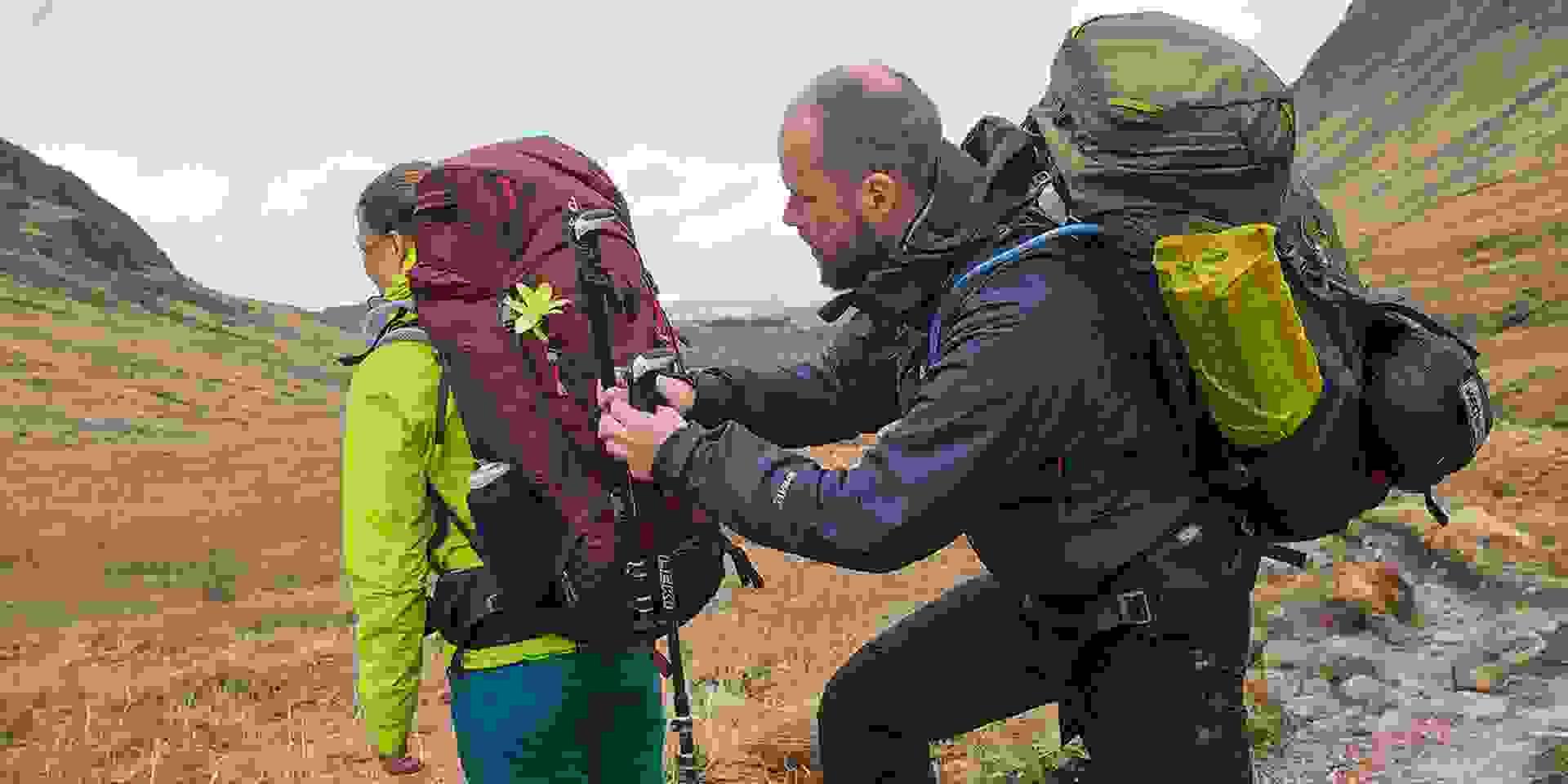Ein Mann stellt die Schlaufen des Rucksacks einer Frau richtig ein.