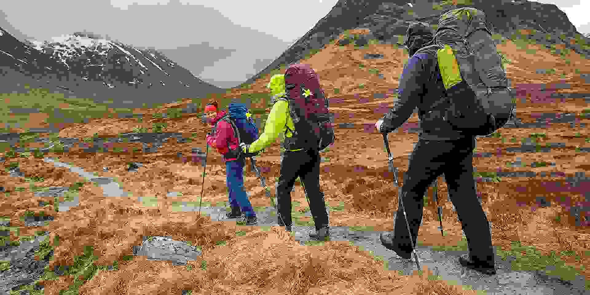 Eine Gruppe Wanderer läuft durch die schottischen Highlands während es bewölkt ist.