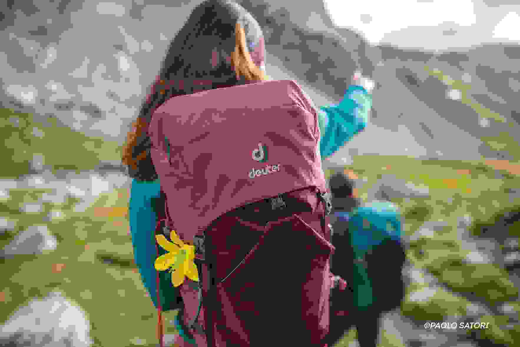 Eine Wandrerin mit Rucksack auf dem Rücken zeigt den Weg