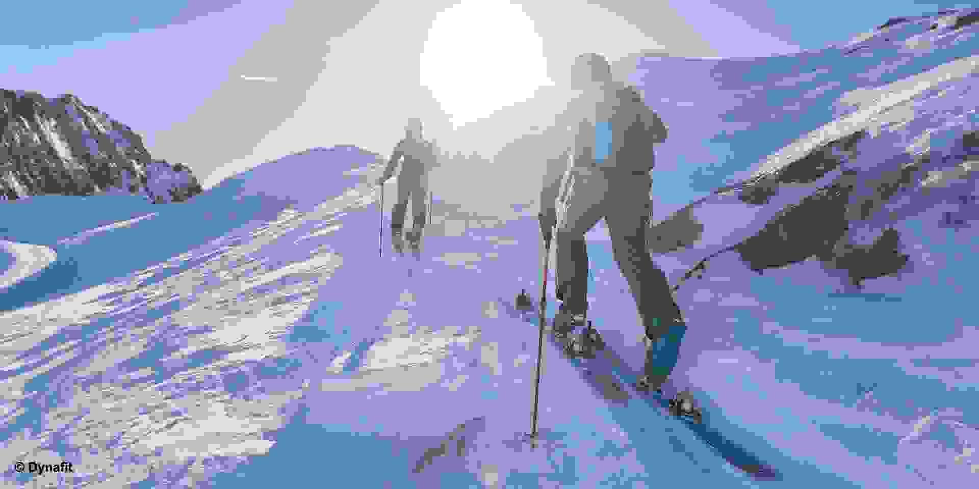 Zwei Skitourengeher queren im Aufstieg schnell einen steilen Hang