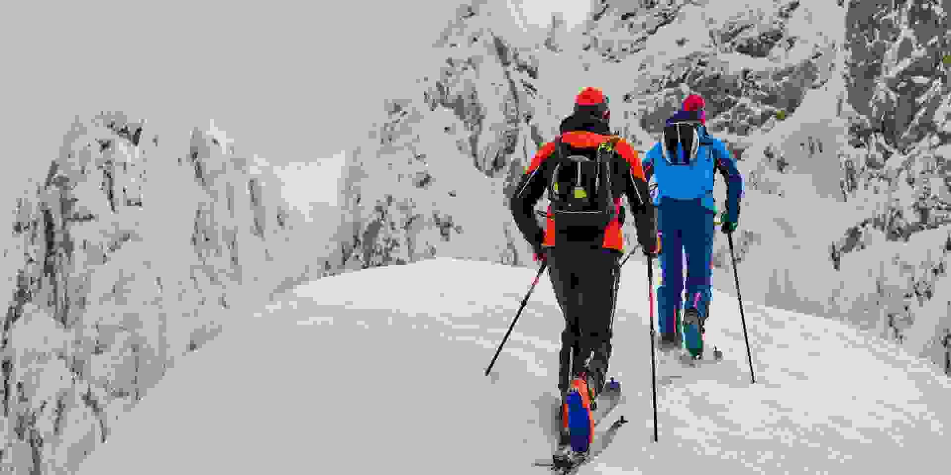 Zwei Skitourengeher auf Skihochtour gehen auf eine Felswand zu.