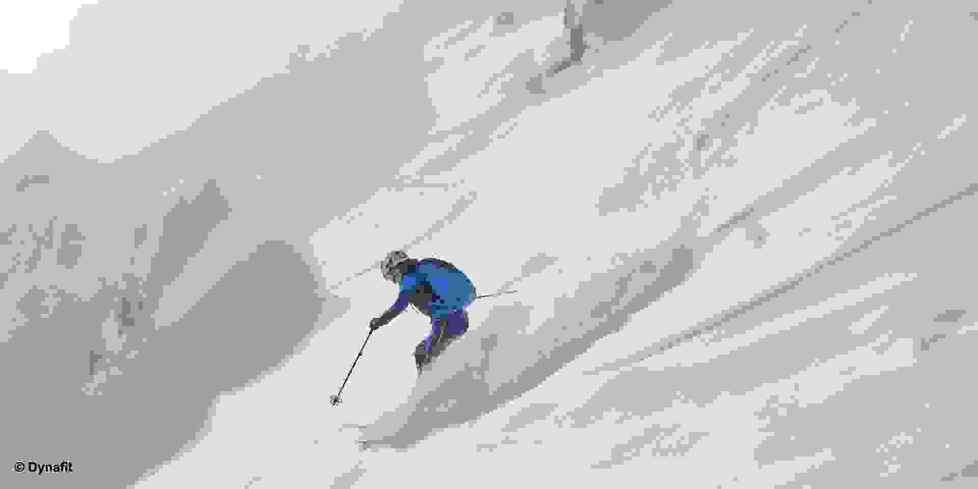 Ein Skitourengeher fährt einen Hang mit frischem Tiefschnee hinab.