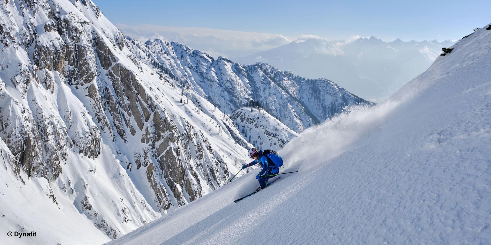 Ein Skitourengeher fährt durch frischen Tiefschnee.