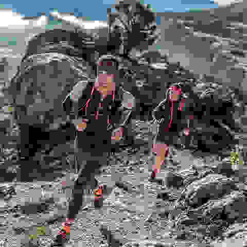 Zwei Trailrunner laufen einen Trail im Hochgebirge.