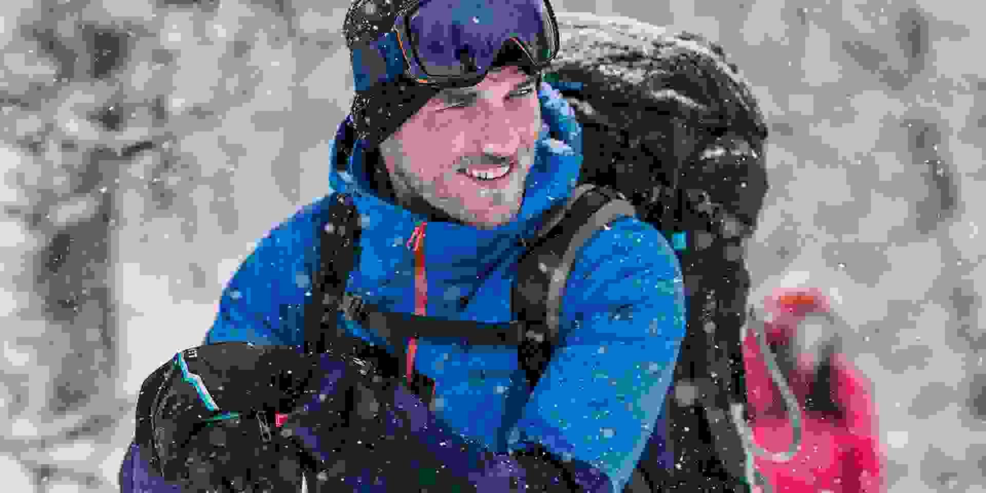 Ein Mann trägt eine Schöffel ZipIn! Jacke während er in einem verschneiten Wald steht.