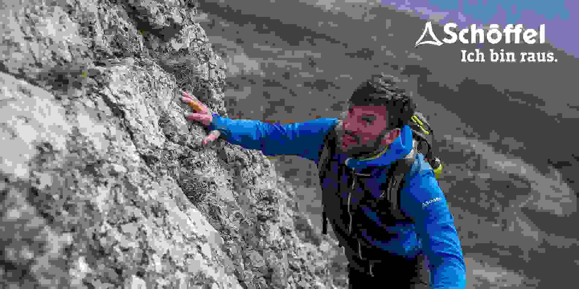 Ein Mann trägt eine Schöffel ZipIn! Jacke während er eine einfachere Kletterstelle überwindet.