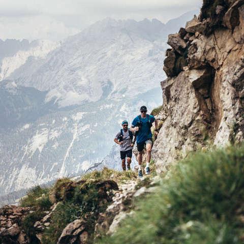 Zwei Trailrunner laufen voll ausgestattet einen Trail im Gebirge entlang.