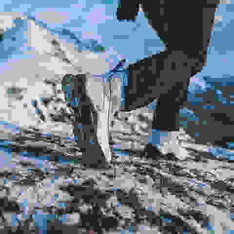 Ein Wanderer geht mit Winter-Wanderschuhen durch eine verschneite Berglandschaft