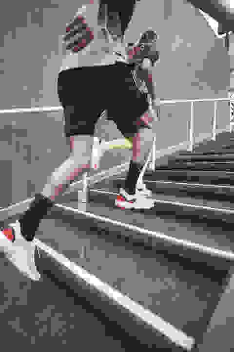 Ein Mann und eine Frau laufen die Treppen hinauf. Dargestellt ist der Vorfusslauf. Der natürliche Laufstil des Menschen.