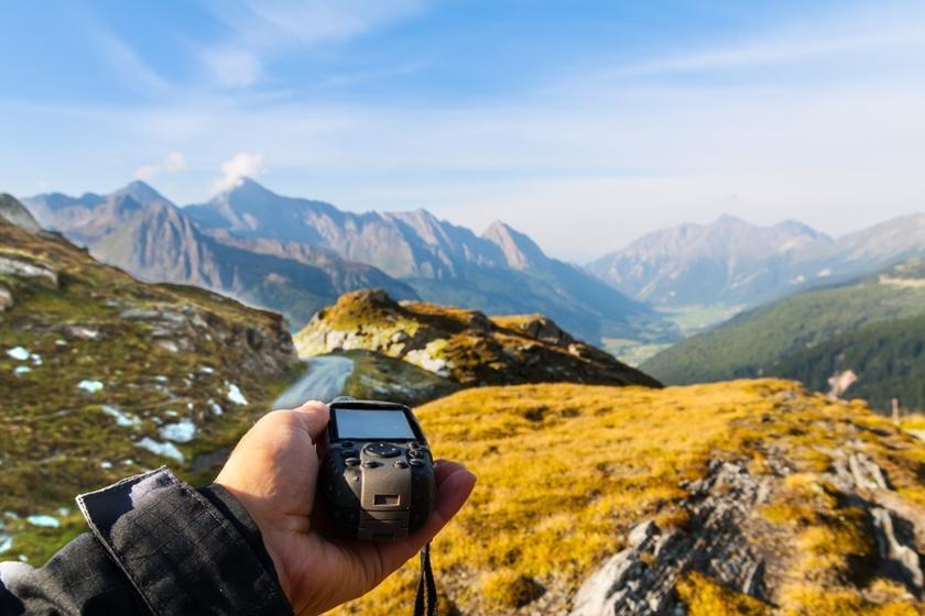 Ein Navigationsgerät von einem Mann in der Hand gehalten.