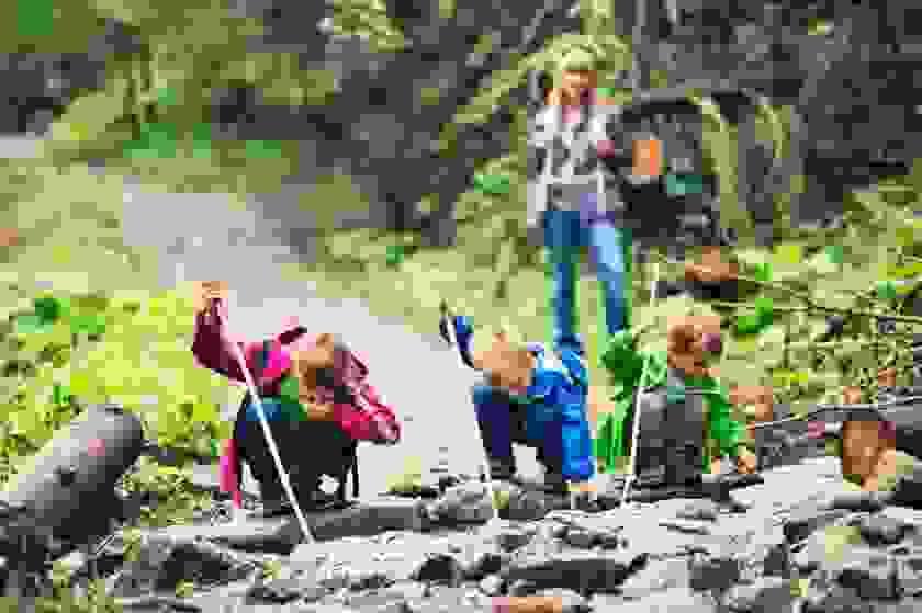 Drei Kinder schauen sich Steine im Wald an. Sie haben alle einen Wanderstock in der Hand. Die Mutter steht im Hintergrund und schaut ihnen zu.