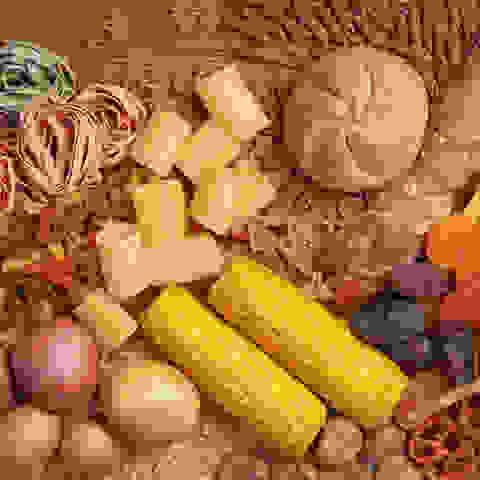 Viele kohlenhydratreiche Lebensmittel auf Stroh drapiert.