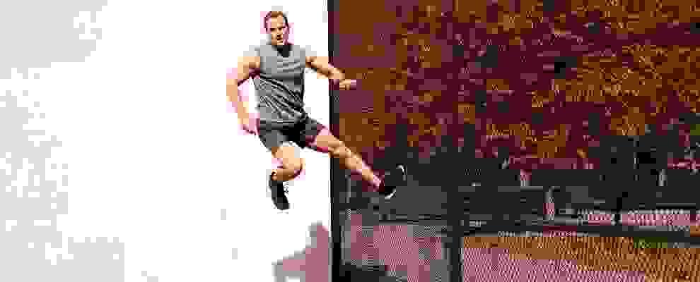 Ein Mann springt gegen einen schwarzen Zaun und scheint in der Luft zu schweben.
