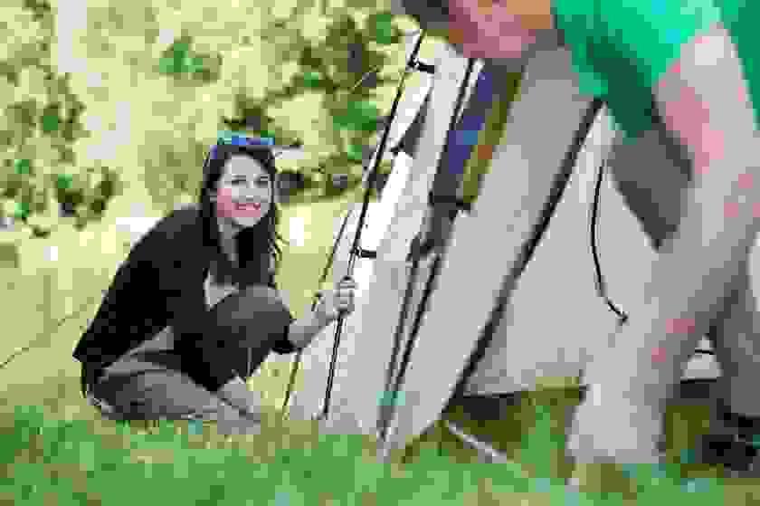Ein Pärchen stellt ein Zelt auf einer grünen Wiese auf.