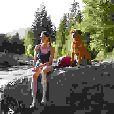 Eine Frau macht nach dem joggen mit ihrem Hund am See eine Pause