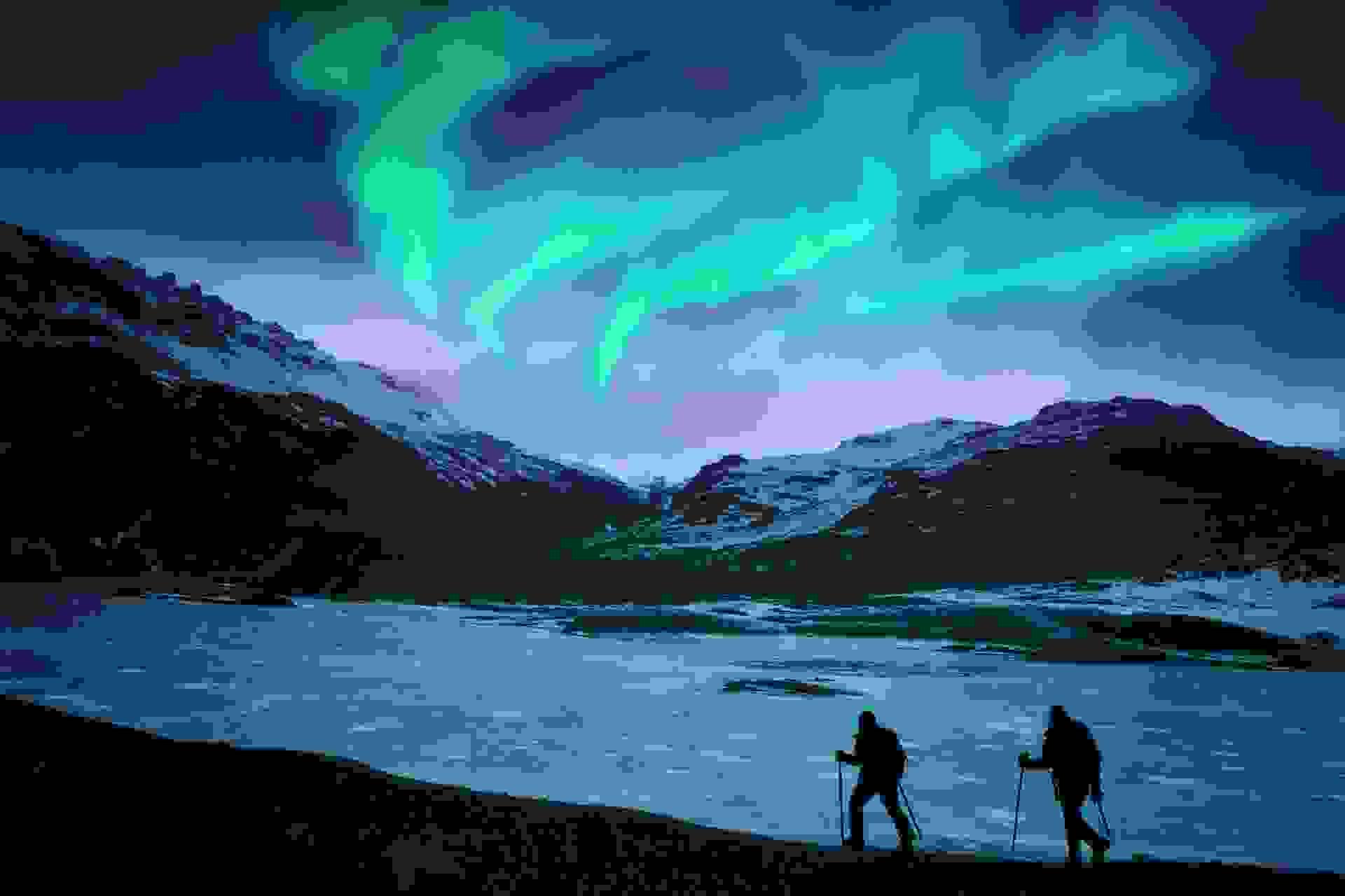 Zwei Nachtwanderer laufen an einem Fjord entlang während am Himmel Polarlichter leuchten