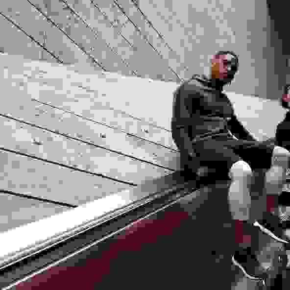 Ein Mann in schwarzem Hoodie, weißer Trainingshose und schwarzer Lauftights steht an einem silbernen Rolltor mit seinem Handy in der Hand.