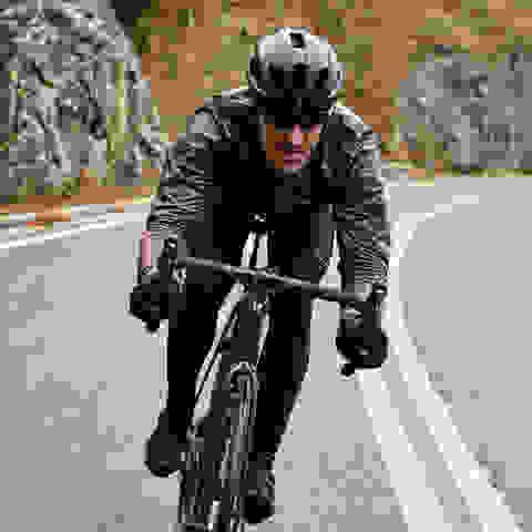 Mann auf Rennrad fährt Straße hinab.