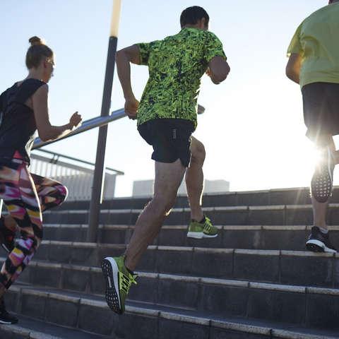 Drei Läufer laufen beim Training nebeneinander her.