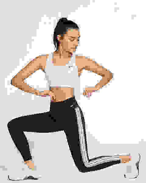 Eine Frau macht Kniebeugen mit der Front zur Kamera. Sie trägt einen weißen Nike Swoosh Sport-BH mit mittlerem Halt.