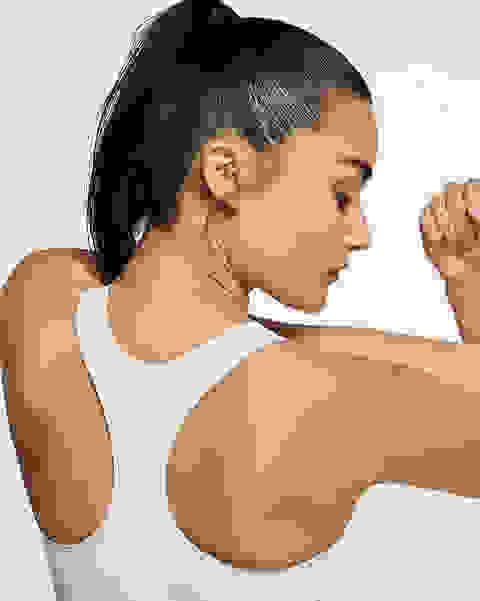 Eine Frau steht mit dem Rücken zur Kamera und dehnt ihre Arme. Sie trägt einen weißen Nike Swoosh Sport-BH mit mittlerem Halt.