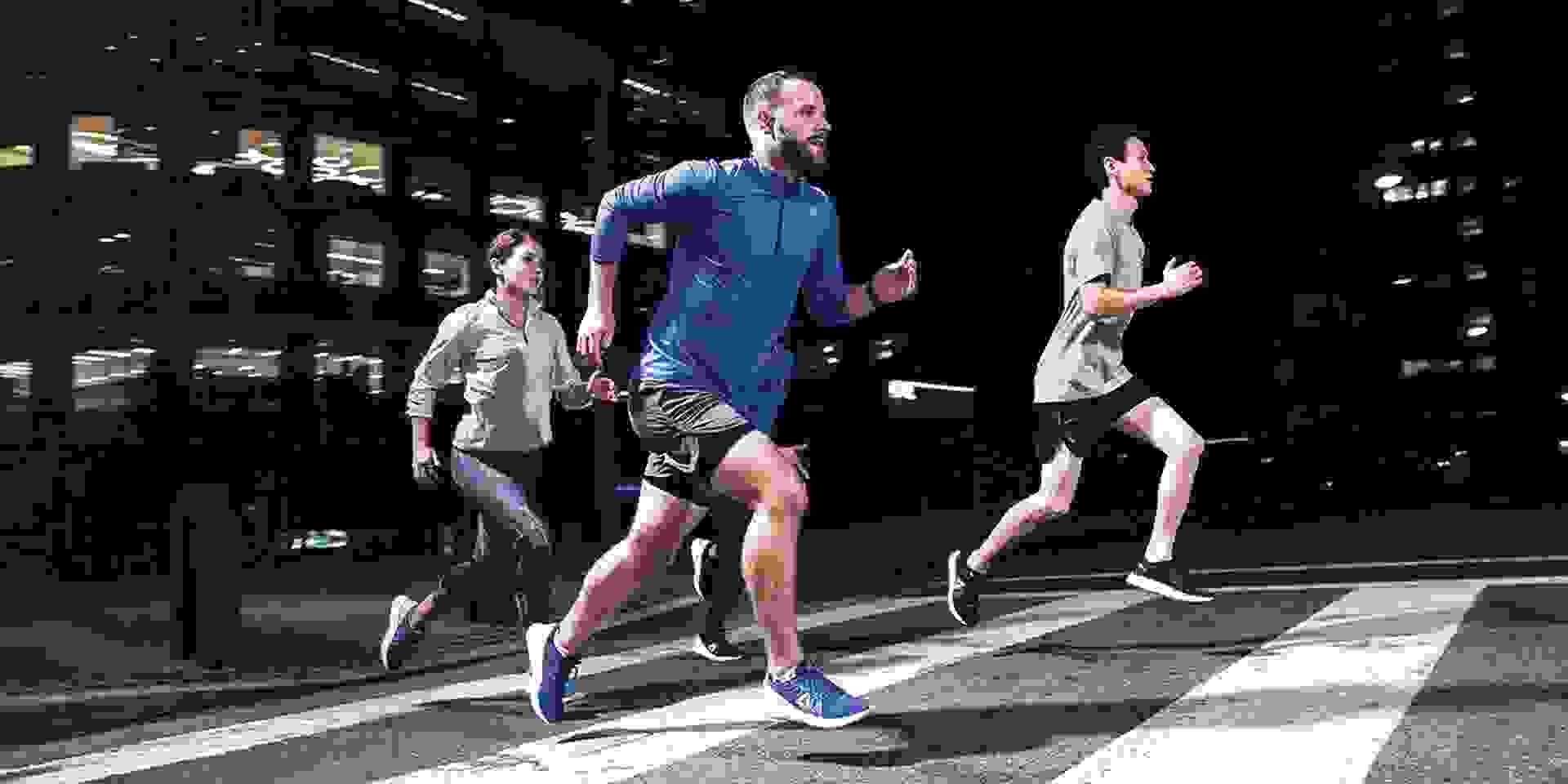 Eine Gruppe Läufer trainiert in der Stadt und läuft über einen Zebrasteifen