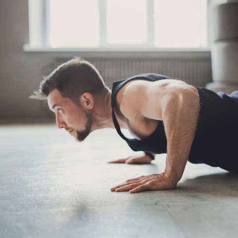 Ein Mann trainiert an einem Schlingentrainer und macht dabei ein sehr angestrengtes Gesicht.