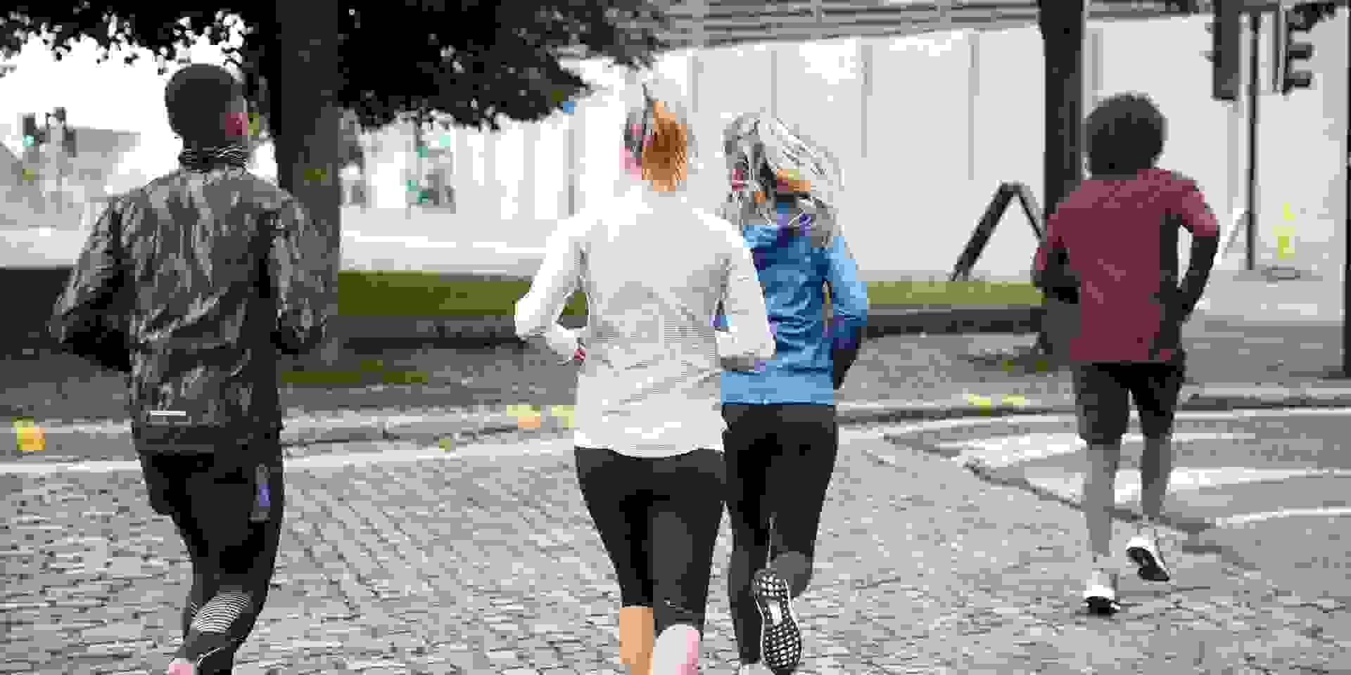 Eine Gruppe Läufer von Hinten die in der Stadt trainieren