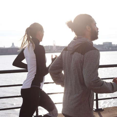 Ein Mann und eine Frau laufen am Hafen entlang.