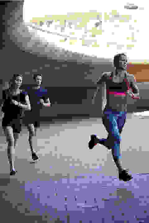 3 Läufer laufen unter einer Unterführung hindurch.