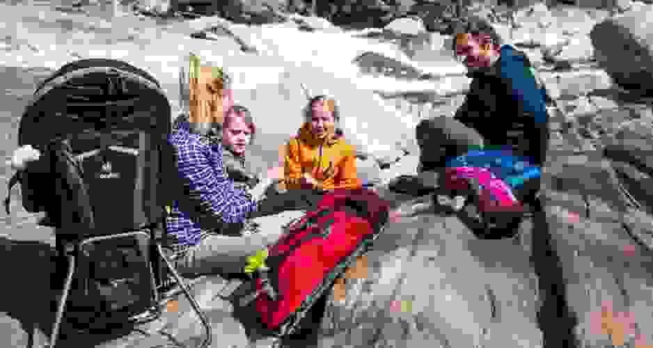 Eine vierköpfige Familie ruht sich während einer Wanderung auf großen Steinen am Rande eines Flusses aus. Jeder hat seinen eigenen Rucksack dabei.