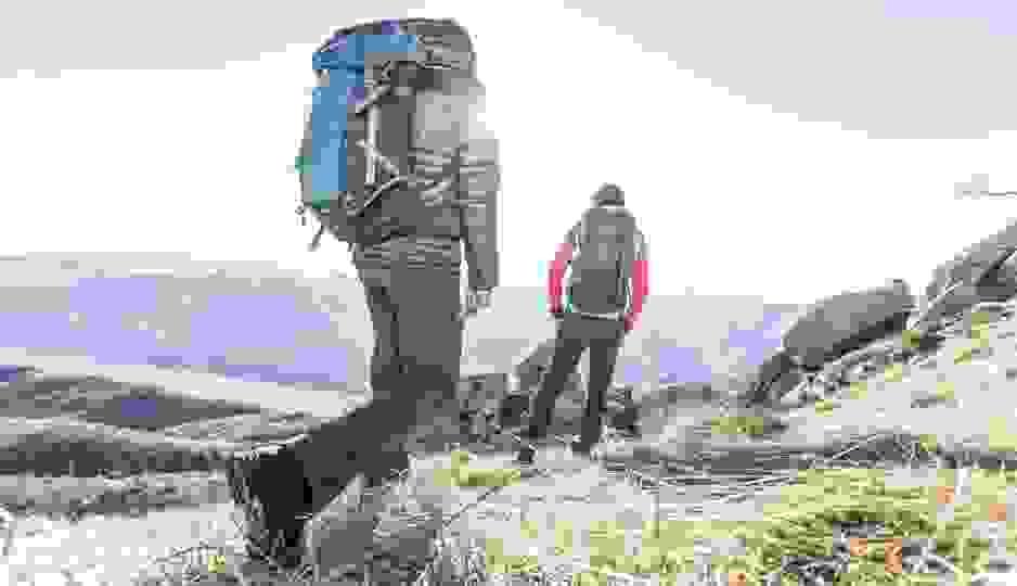 2 Männer auf Wandertour in den Bergen. Auf den Rücken trägen sie große Wanderrucksäcke.