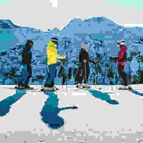 Eine Gruppe Skifahrer macht sich zur Abfahrt bereit.
