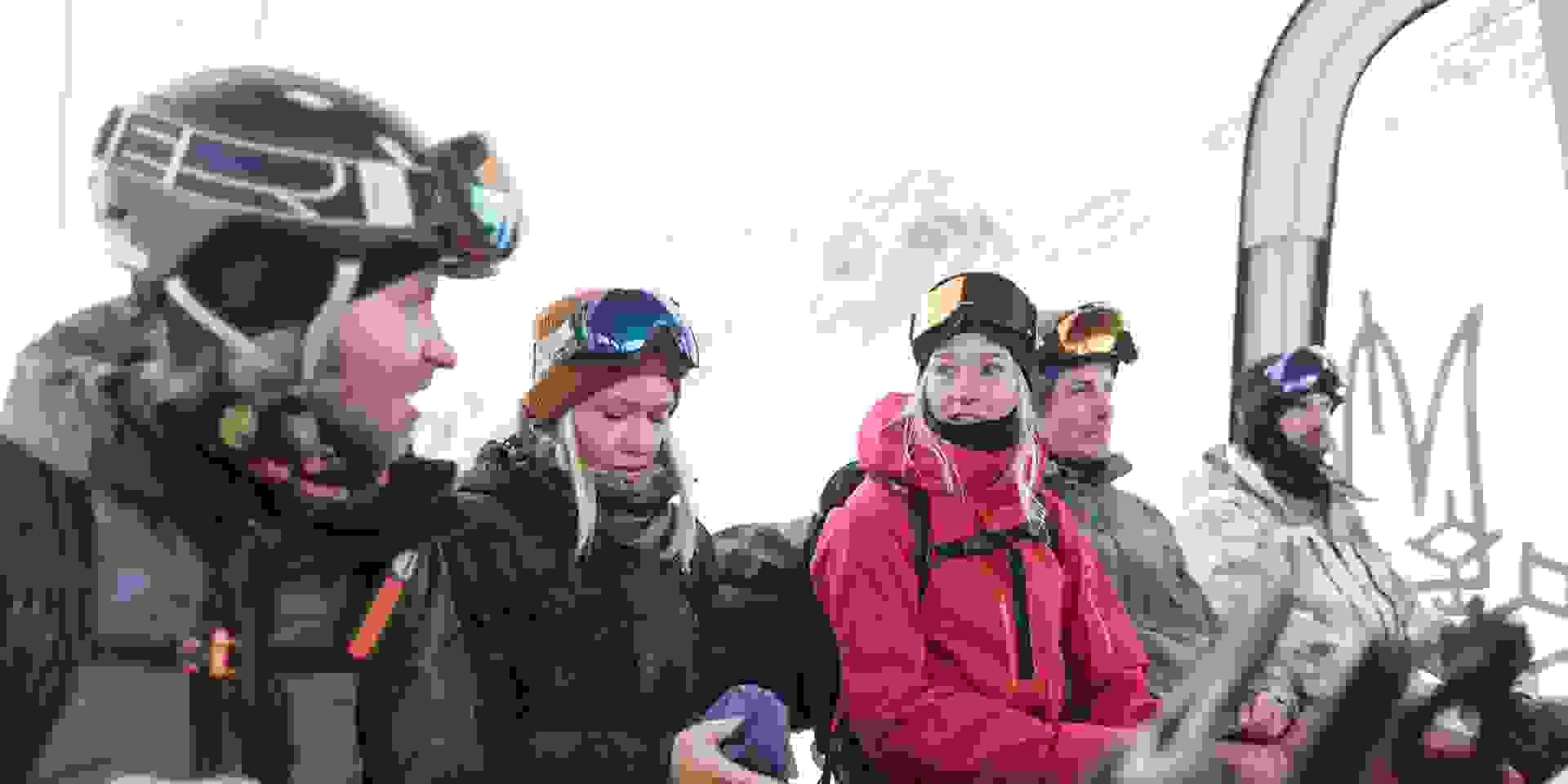 Eine Gruppe Snowboarder sitzt in der Kabine einer Gondel.
