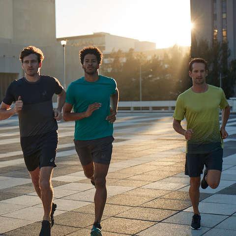 Drei Läufer laufen in der Dämmerung durch die Stadt.