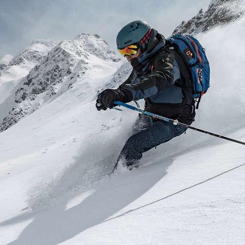 Ein Skifahrer rast die Piste im Tiefschnee hinab.