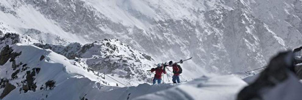 2 Bergsteiger haben ihre Skier geschultert und wandern durch eine verschneite Berglandschaft.