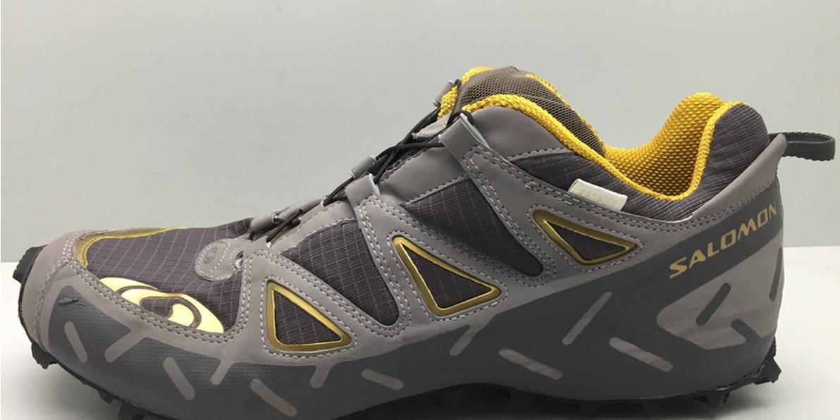 Ein Salomon Speedcross Trailrunning Schuh in grau mit gelben Applikationen.