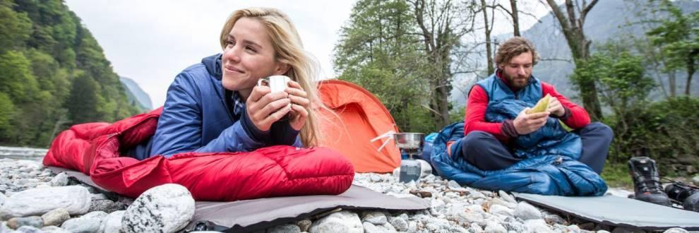 Ein Mann und eine Frau liegen an einem Flußufer in ihren Schlafsäcken.
