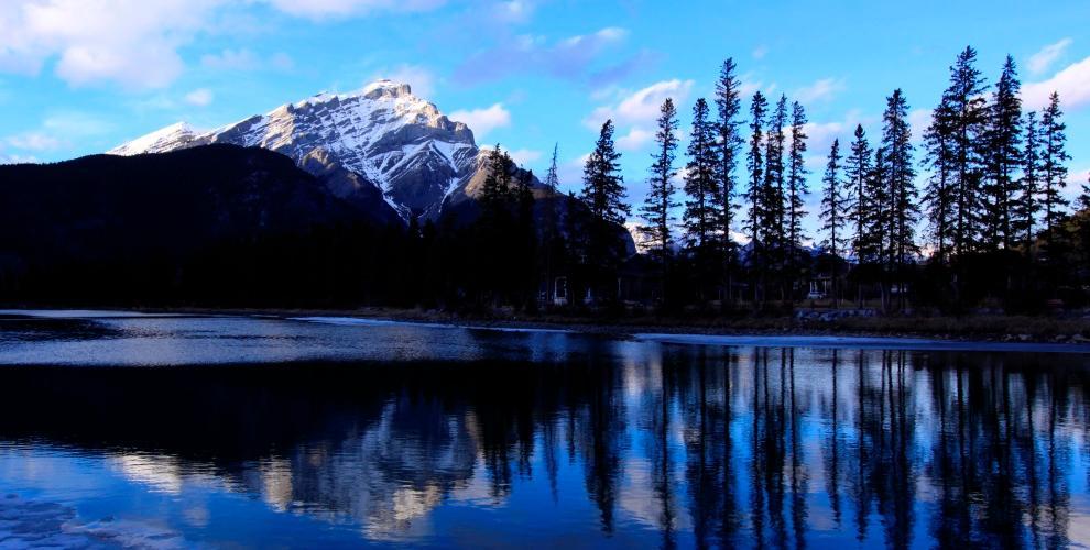 Ein See in Kanada. Im Hintergrund ist ein schneebedeckter Berg zu sehen.