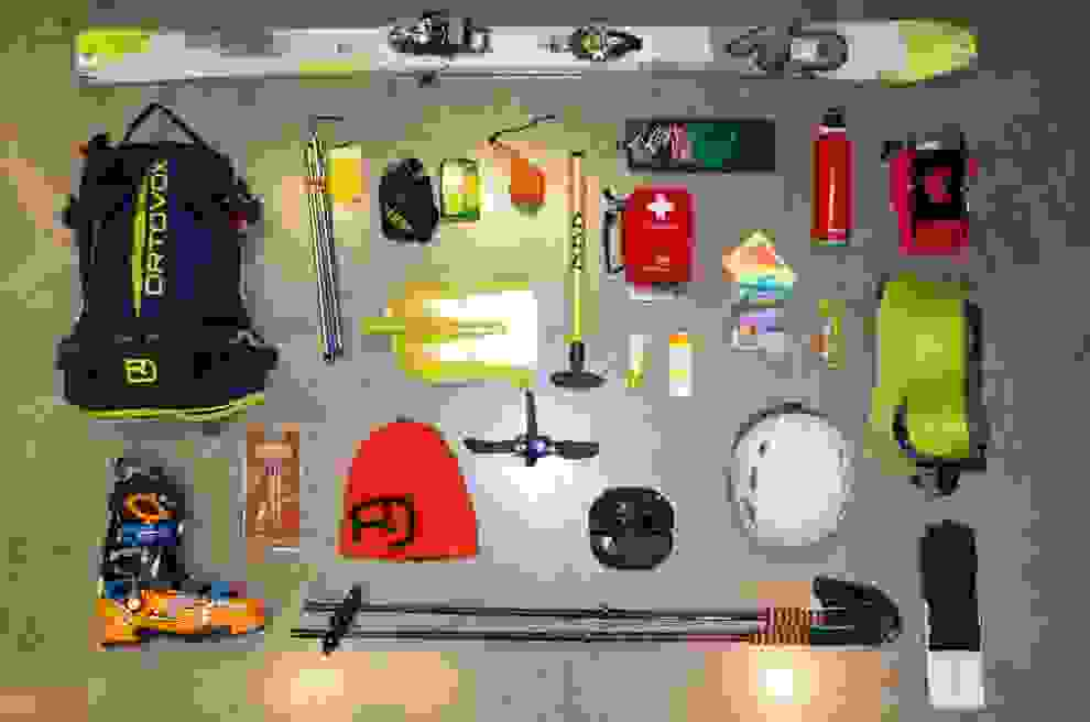 Eine bunte Ansammlung von Ausrüstungsgegenständen, die bei einer Skitour unbedingt dabei sein sollten.