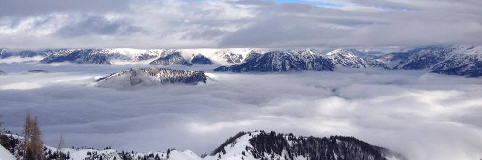 Eine Gebirgskette auf einer Höhe, wo bereits Wolken vorhanden sind und nur die Gipfel zu sehen sind.