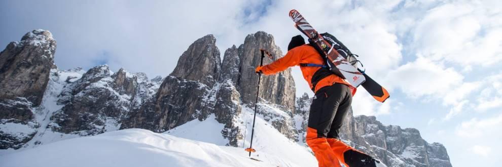 Ein Skitourer fährt bergauf und hat einen Rucksack voll nützlicher Ausrüstung auf dem Rücken.