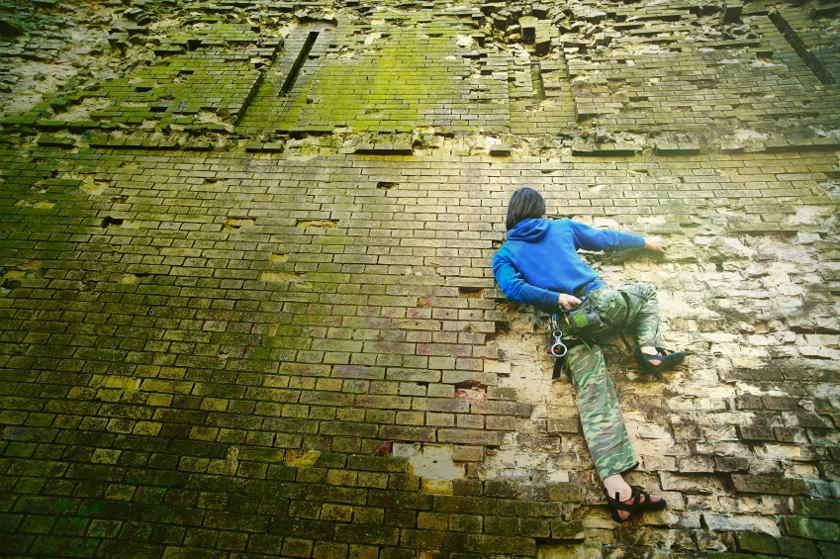 Ein Boulderer klettert eine Backsteinmauer hinauf.