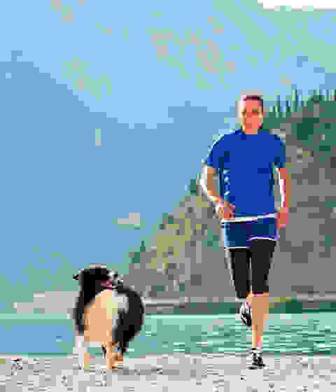 Sonja von Opel läuft mit ihrem Hund an einem See entlang